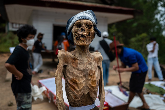 """Family members clean the preserved body of their relative during a traditional ritual called """"Manene"""" in Panggala, Nort Toraja, South Sulawesi, Indonesia, Tuesday, August 25th 2020. (Photo by Hariandi Hafid/ZUMA Wire/Rex Features/Shutterstock)"""