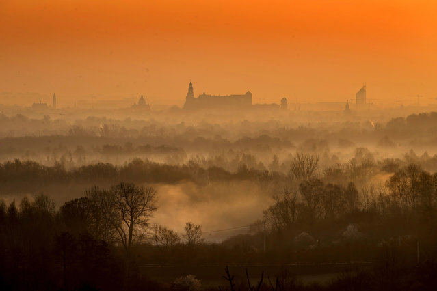 The sun rises over the city, revealing a whispy blanket of smog, in Krakow, southern Poland, 07 April 2020. Despite the movement restrictions implemented in a bid to slow down the spread of the pandemic COVID-19 disease caused by the SARS-CoV-2 coronavirus, air pollution levels across Polish cities still remain relatively high. (Photo by Lukasz Gagulski/EPA/EFE)