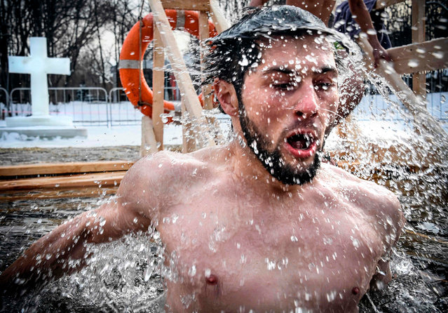 An Orthodox believer plunges into the icy waters of a pond during the celebration of the Epiphany holiday in Moscow on January 19, 2018. (Photo by  Alexander Nemenov/AFP Photo)