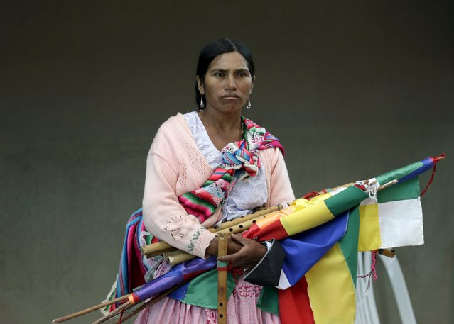 """A woman holds flags and traditional music instruments during the inauguration of a sports arena called """"Coliseo Ban Ki-Moon"""" in Vila Vila, south of Cochabamba, October 11, 2015. (Photo by David Mercado/Reuters)"""