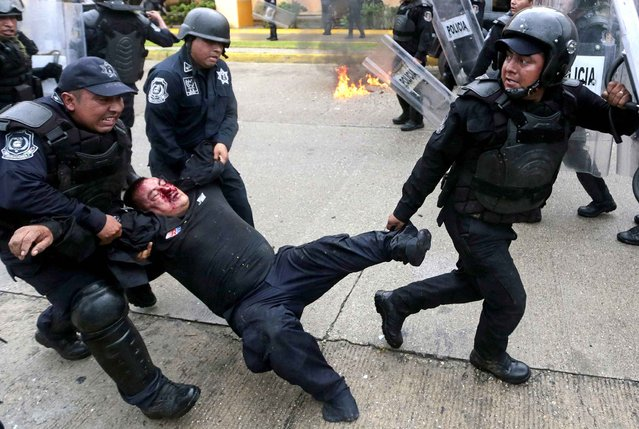 A wounded riot police officer is rescued from violent demonstrators during clashes that erupted during a protest against the suspected massacre of 43 missing Mexican students, in the proximities of Acapulco's airport, in the Mexican state of Guerrero State, on November 10, 2014. Protesters angry at the suspected massacre threw stones and a firebomb at riot police in the Pacific resort of Acapulco, injuring 11 officers. (Photo by Pedro Pardo/AFP Photo)