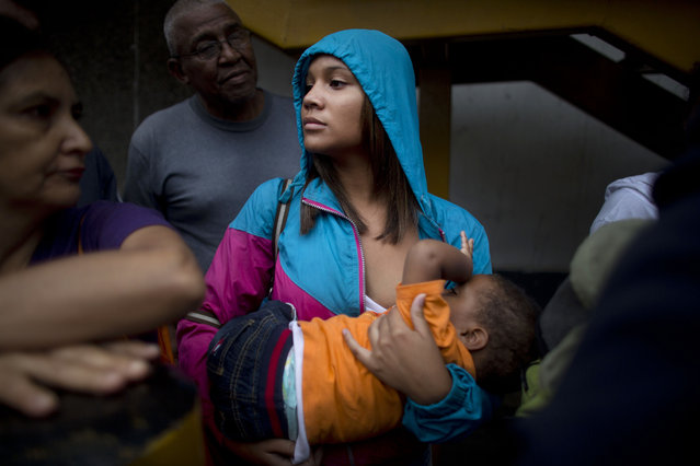 In this Tuesday, May 3, 2016 photo, Madeley Vasquez, 16, breast feeds her one-year-old son Joangel as she waits in line outside a supermarket to buy food in Caracas, Venezuela. Vasquez once ran down the block to avoid getting caught up in a knife fight that broke out when a woman was accused of cutting the line. (Photo by Ariana Cubillos/AP Photo)