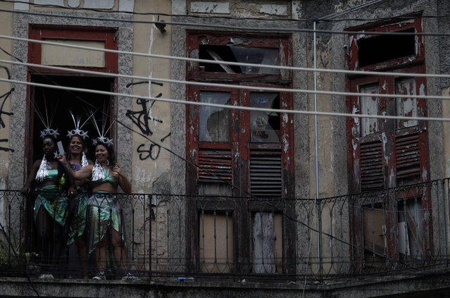 Revellers stand at the window of a house during the annual block party Escravos da Maua as part of pre-carnival festivities in Rio de Janeiro, Brazil, February 4, 2018. (Photo by Ricardo Moraes/Reuters)