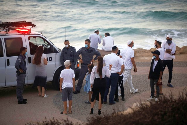 Policemen speak to Israelis by the shore of the Mediterranean after Israel entered a second nationwide lockdown amid a resurgence in new coronavirus disease (COVID-19) cases, forcing residents to stay mostly at home during the Jewish high-holiday season in Tel Aviv, Israel on September 19, 2020. (Photo by Nir Elias/Reuters)