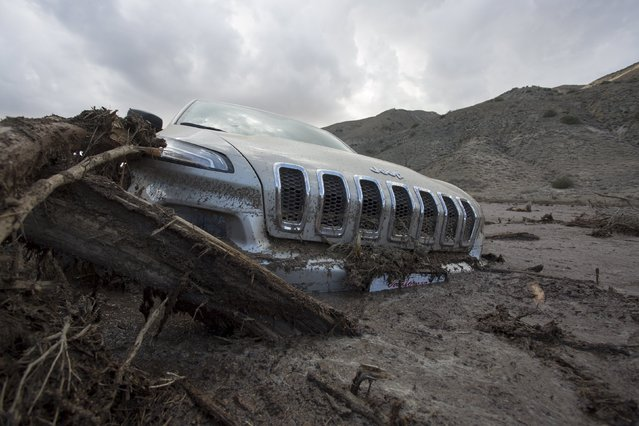 A car remains mired in mud and debris on State Route 58 near Tehachapi, California, about 60 miles (97 km) outside of Los Angeles October 17, 2015. (Photo by David McNew/Reuters)