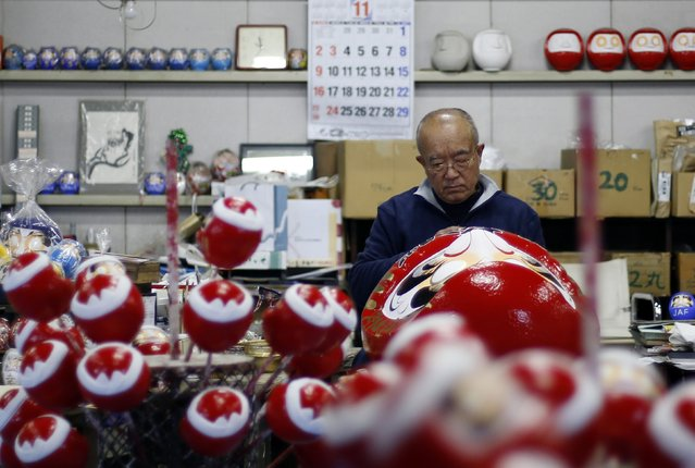 """Japanese craftsman Sumikazu Nakata adds the final touches on a Daruma doll, which is believed to bring good luck, in front of a calendar of November on a wall at his studio  """"Daimonya"""" in Takasaki, northwest of Tokyo November 23, 2014. (Photo by Yuya Shino/Reuters)"""