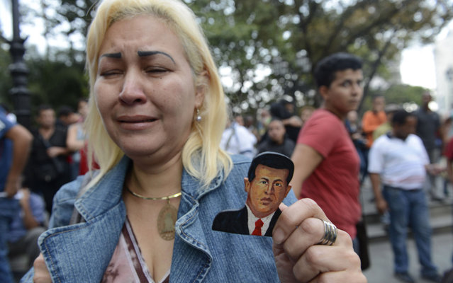 A supporter of Venezuelan President Hugo Chavez cries after knowing of his death in Caracas on March 5, 2013. (Photo by Juan Barreto/AFP Photo)