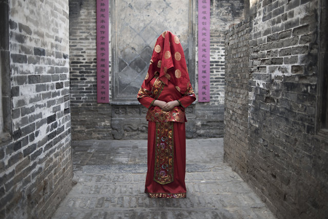 "A Chinese woman dressed with a traditional bride costume, poses during a wedding performance as part of the She Huo festival, to celebrate the Lunar New Year, marking the Year of the Dog, in Hancheng, Shaanxi province, on February 16, 2018. The Lunar New Year falls on February 16 this year, with celebrations in China scheduled to last for a week. She Huo festival, celebrated in the northwestern China, is a festival dedicated to the gods of earth and fire. ""She"" literally means ""God of Earth"" and huo means ""God of Fire"". (Photo by Fred Dufour/AFP Photo)"