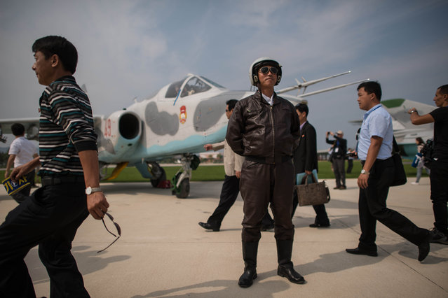 Spectators walk pass a pilot, as he poses with a Sukhoi aircraft during the second day of the Wonsan Friendship Air Festival in Wonsan on September 25, 2016. (Photo by Ed Jones/AFP Photo)