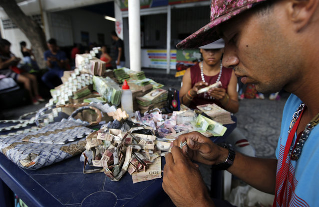 In this February 22, 2018 photo, Richard Segovia, right, weaves Venezuelan Bolivars to create bags and art for sale in La Parada, Colombia, on the border with Venezuela. With his earnings, he manages to send around $15 to his family in Caracas whenever he can. (Photo by Fernando Vergara/AP Photo)