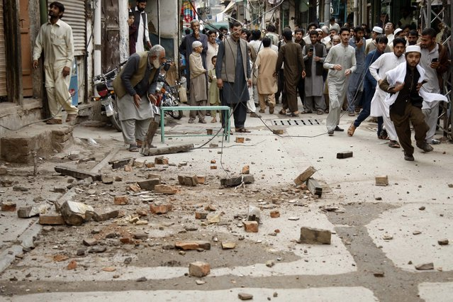 People react following a 7.7 magnitude earthquake, in Peshawar, Pakistan, 26 October 2015. (Photo by Arshad Arbab/EPA)