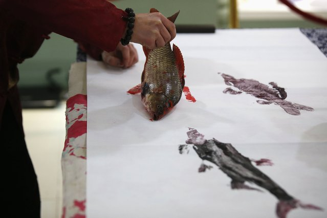 Folk artist Han Xiaoming demonstrates block printing with a live fish in Hangzhou, Zhejiang province December 4, 2014. (Photo by Aly Song/Reuters)