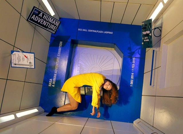 "A visitor poses for a photograph in the gravity experimental module at the ""NASA – A Human Adventure"" space exhibition in Bangkok, Thailand, 01 December 2014. The exhibition showcases 350 original artifacts including some which were used in a real space operations from the NASA space program. The exhibition runs from 01 December to 01 February 2015. (Photo by Rungroj Yongrit/EPA)"