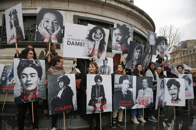 Women hold posters of famous feminists during a gathering to mark International Women's Day in Paris, Thursday, March 8, 2018. Statistics show at the same age and equivalent job, there is a 9 percent gap between the wages of men and women in France. (Photo by Michel Euler/AP Photo)