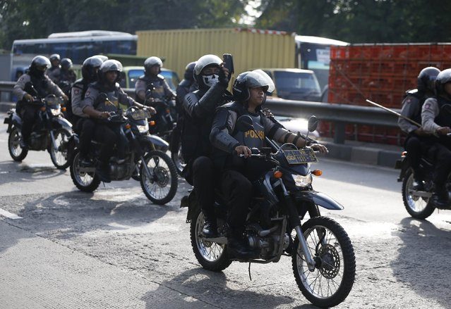 A policeman takes pictures as he rides on a motorcycle towards a workers' rally in Tangerang, December 11, 2014. Hundreds of workers held the protest demanding the government to raise minimum wages after the government's decision to raise subsidized fuel price, local paper reported on Wednesday. (Photo by Reuters/Beawiharta)