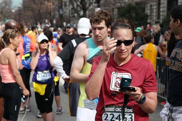 Runners react near Kenmore Square after two bombs exploded during the 117th Boston Marathon on April 15, 2013 in Boston, Massachusetts. (Photo by Alex Trautwig)
