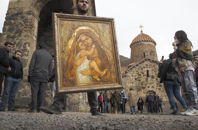 A man holds an icon from the Dadivank, an Armenian Apostolic Church monastery dating to the 9th century, as ethnic Armenians leave the separatist region of Nagorno-Karabakh to Armenia, Saturday, November 14, 2020. (Photo by Dmitry Lovetsky/AP Photo)
