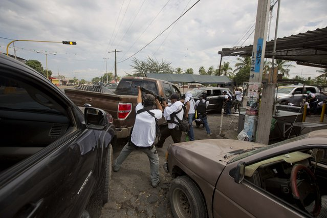 "In this January 12, 2014 file photo, the Self-Defense Council of Michoacan (CAM) engage in a firefight as they try to flush out alleged members of the Knights Templar drug cartel from Nueva Italia, Mexico. The vigilantes say they are liberating territory in the ""Tierra Caliente"" and are aiming for the farming hub of Apatzingan, said to be the cartel's central command. (Photo by Eduardo Verdugo/AP Photo)"