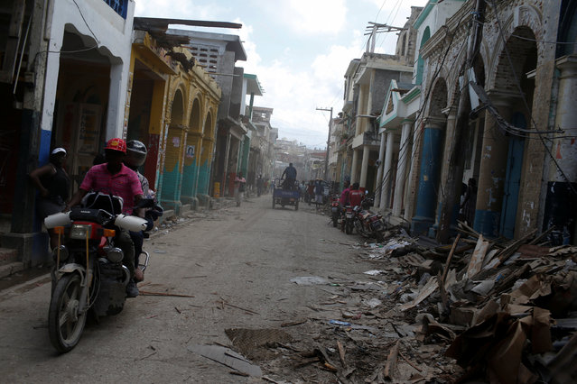 A motorcyclist drives past destroyed houses after Hurricane Matthew hit Jeremie, Haiti, October 10, 2016. (Photo by Carlos Garcia Rawlins/Reuters)