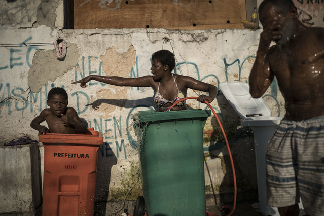 In this September 11, 2017 photo, people use tall trash containers to shower outside their squatter building that used to house the Brazilian Institute of Geography and Statistics (IBGE) in the Mangueira slum of Rio de Janeiro, Brazil. The World Bank estimates that between the start of 2016 and the end of this year, 2.5 million to 3.6 million Brazilians will have fallen back below the poverty line of 140 Brazilian reais per month, about $44 at current exchange rates. (Photo by Felipe Dana/AP Photo)