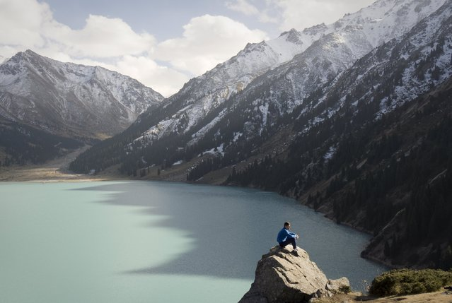 A tourist rests on a rock in front of the Bolshoy (Big) Almaty lake at 2,600 meters (8530 ft) above sea level at a sunny autumn day in a mountains outside Almaty, Kazakhstan, October 4, 2015. (Photo by Shamil Zhumatov/Reuters)