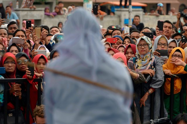 Onlookers witness a public flogging in front of a mosque in the provincial capital Banda Aceh on April 20, 2018. (Photo by Chaideer Mahyuddin/AFP Photo)