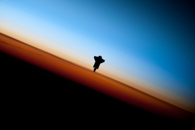 The space shuttle Endeavour is silhouetted against the backdrop of Earth's horizon prior to docking with the International Space Station in this picture taken by an Expedition 22 crew member on February 9, 2010 and released by NASA February 12, 2010. (Photo by NASA)