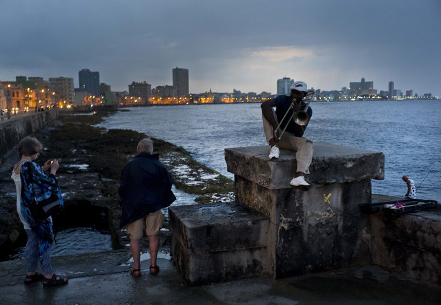 """In this April 13, 2018 photo, musician Lazaro Martinez poses with his trombone on the Malecon sea wall in Havana, Cuba. Since 1991, Martinez has regularly played his music at the Malecon. """"My politics are music"""", said the 52-year-old. (Photo by Ramon Espinosa/AP Photo)"""