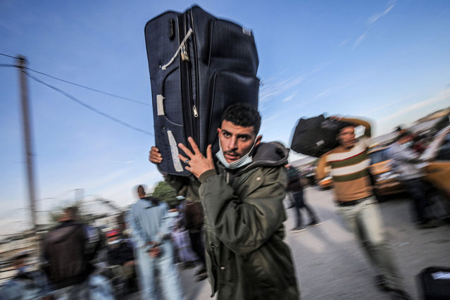 A man walks carrying a suitcase as Palestinians wait to cross onto the Egyptian side, through the Rafah border crossing between the Gaza Strip and Egypt, on November 24, 2020. It was announced that Egypt would reopen the Rafah border crossing from November 24 to 26. (Photo by Said Khatib/AFP Photo)