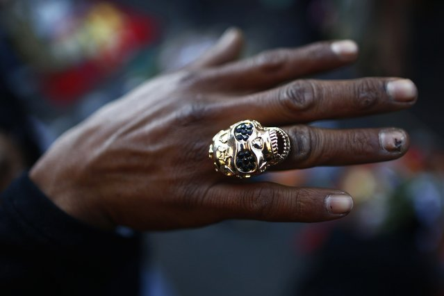 A follower shows a ring of La Santa Muerte (The Saint of Death), a cult figure often depicted as a skeletal grim reaper, near at the saint's altar at Tepito neighborhood, in Mexico City January 1, 2015. Followers gather at the saint's altar at the start of the new year to leave offerings of apples, flowers, cigarettes, coloured candles and tequila to thank the saint for favours that have been granted and to ask for new ones in the new year. (Photo by Edgard Garrido/Reuters)