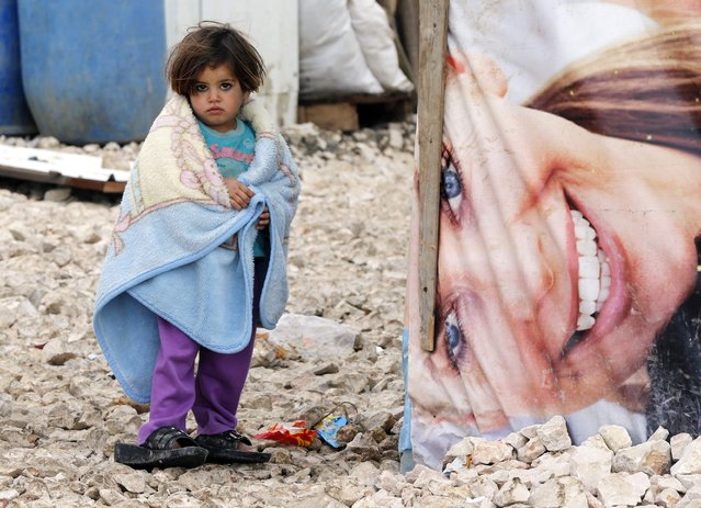 A Syrian refugee girl covers herself with a blanket as she stands outside tents at a makeshift settlement in Bar Elias in the Bekaa valley January 5, 2015. Lebanon enforced new immigration controls at the Syrian border on Monday in a move to gain control of the steady stream of refugees from its much larger neighbour. (Photo by Mohamed Azakir/Reuters)