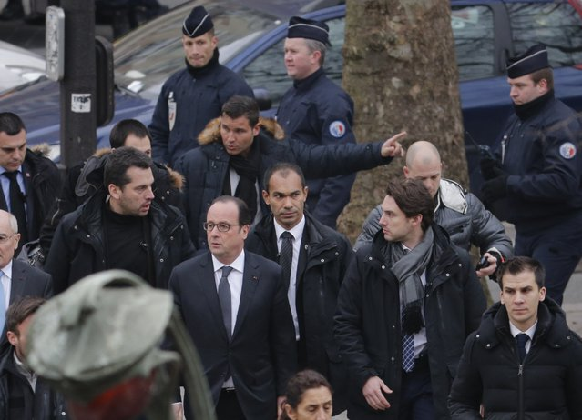 French President Francois Hollande (C) arrives after a shooting at the Paris offices of Charlie Hebdo, a satirical newspaper, January 7, 2015. Eleven people were killed and 10 injured in shooting at the Paris offices of the satirical weekly Charlie Hebdo, already the target of a firebombing in 2011 after publishing cartoons deriding Prophet Mohammad on its cover, police spokesman said. (Photo by Christian Hartmann/Reuters)