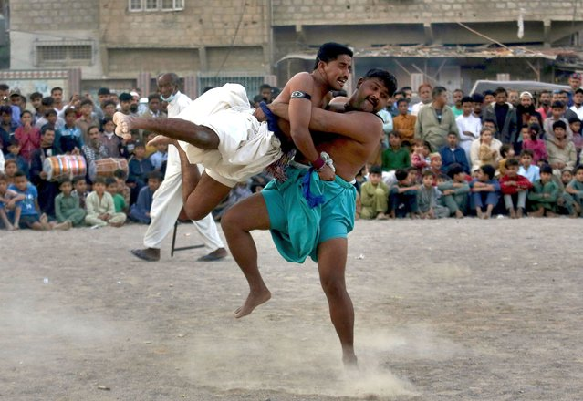 """Wrestlers compete in an ancient Sindhi form of wrestling called """"Malakhra"""" in Karachi, Pakistan, Sunday, December 13, 2020. The match begins with both wrestlers tying a twisted cloth around the opponent's waist. Each one then holds onto the opponent's waist cloth and tries to throw him to the ground. (Photo by Fareed Khan/AP Photo)"""