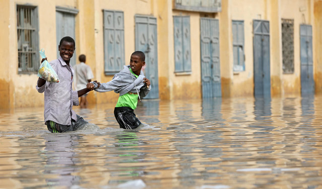 Residents wade through a flooded street in Hamerweyne district of Mogadishu, Somalia May 20, 2018. (Photo by Feisal Omar/Reuters)