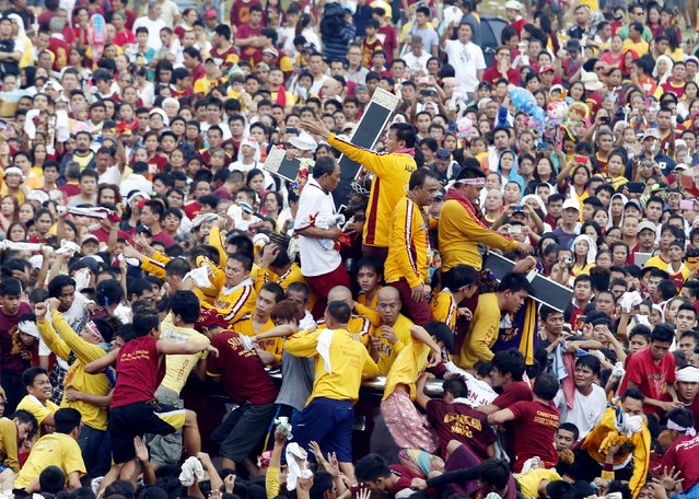 The carriage carrying the Black Nazarene makes it way through thousands of people as it is pulled by devotees during an annual procession in Manila, January 9, 2015. (Photo by Erik De Castro/Reuters)