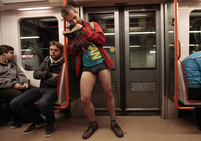 """A passenger not wearing pants reads a book as he stands in a subway train during the """"No Pants Subway Ride"""" in Prague January 11, 2015. (Photo by David W. Cerny/Reuters)"""