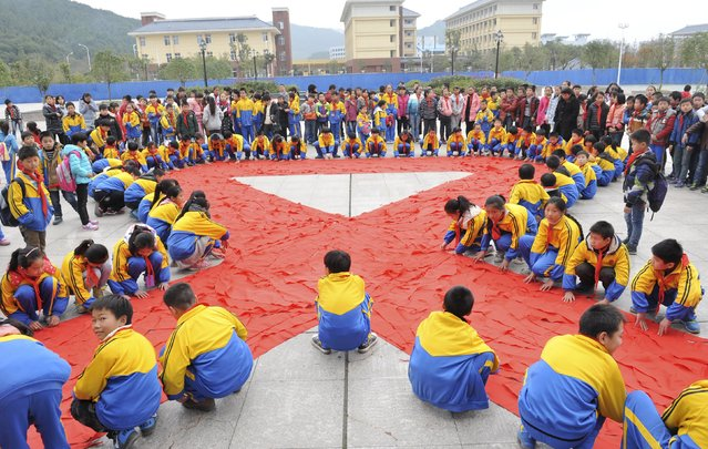 Primary school students use their red scarfs to form a giant ribbon to mark the World AIDS Day in Dexing, Jiangxi province, China, November 30, 2015. (Photo by Reuters/China Daily)