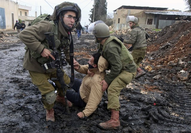 Israeli soldiers arrest a Palestinian protester during clashes following a protest against the near-by Jewish settlement of Qadomem, in the West Bank village of Kofr Qadom near Nablus January 16, 2015. (Photo by Abed Omar Qusini/Reuters)