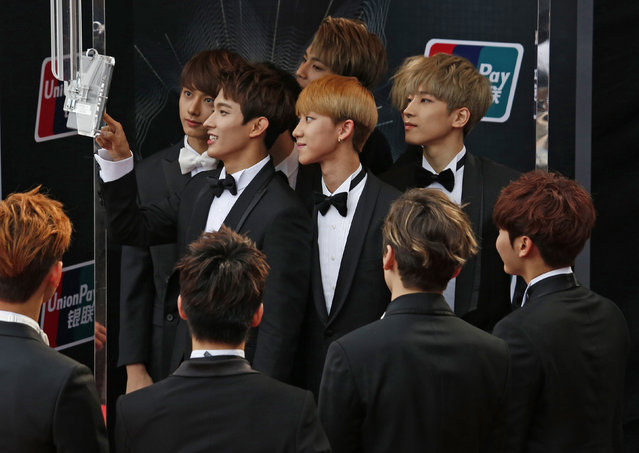 Members of the South Korean band SEVENTEEN react in front of an official camera on the red carpet during 2015 Mnet Asian Music Awards (MAMA) in Hong Kong, China December 2, 2015. (Photo by Bobby Yip/Reuters)