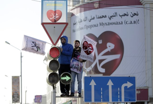 "Men stand at the top of a traffic lights post as they attend a rally to protest against satirical cartoons of prophet Mohammad, in Grozny, Chechnya January 19, 2015. Tens of thousands of people staged the rally on Monday in Chechnya against French magazine Charlie Hebdo's cartoons of the prophet, which the predominantly Muslim region's leader denounced as ""vulgar and immoral"". The posters read, ""Mohammad"". (Photo by Eduard Korniyenko/Reuters)"
