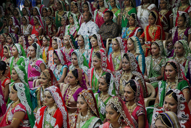 Indian diamond trader Mahesh Savani, top center wearing white, poses for a group photo along with brides before mass wedding hosted by him in Surat, India, Sunday, December 6, 2015. 151 young couples tied the knot at the mass wedding hosted by Savani who has been funding the weddings of fatherless women in the city of Surat for several years. (Photo by Ajit Solanki/AP Photo)