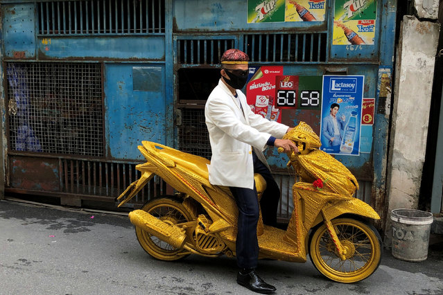 A man rides a golden motorbike on a street in Bangkok, Thailand on August 14, 2020. (Photo by Jorge Silva/Reuters)