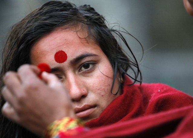A Nepalese woman devotee receives tika, or vermilion powder, on her forehead after taking a holy dip in the Bagmati River during month long Swasthani Bratakatha festival in Kathmandu, Nepal, Tuesday, January 20, 2015. (Photo by Niranjan Shrestha/AP Photo)