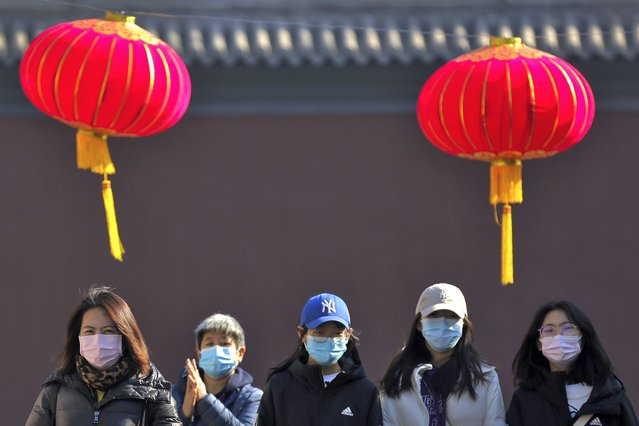 People wearing face masks to help curb the spread of the coronavirus under red lanterns hang ing along on a hutong alley in Beijing, Monday, February 8, 2021. China appears to have stamped out its latest coronavirus outbreaks centered on the northeast, reporting no new cases of local infection in its latest daily report. (Photo by Andy Wong/AP Photo)
