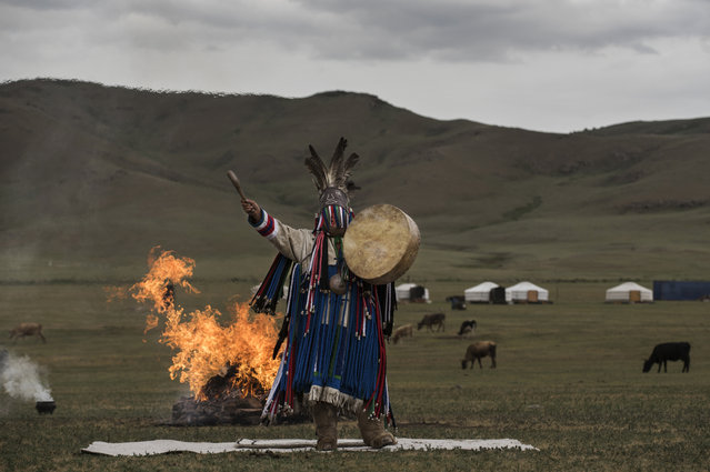 A Mongolian Shaman or Buu, gestures during a fire ritual during a ceremony in the grasslands on June 21, 2018 outside Ulaanbaatar, Mongolia. (Photo by Kevin Frayer/Getty Images)