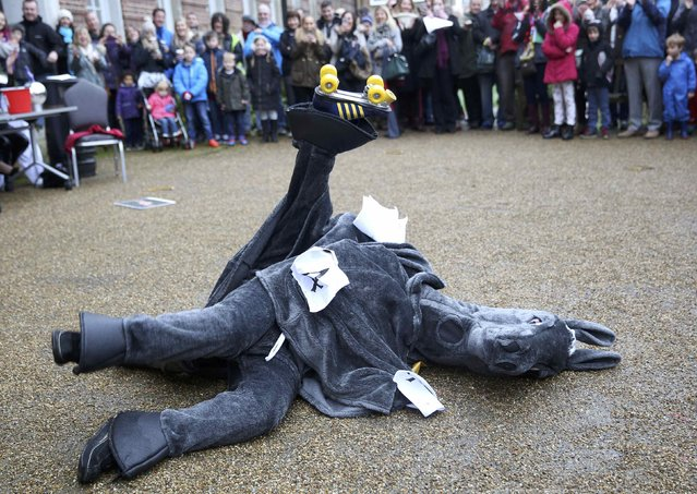 Participants fall as they perform a dance in costume  before the start of the annual London Pantomime Horse Race in Greenwich, Britain December 13, 2015. (Photo by Neil Hall/Reuters)