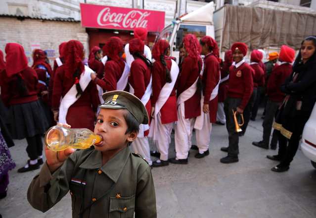 A child dressed in an imitation dress of army soldier enjoys a cold drink during a religious procession in Amritsar, India, 15 December 2015. The religious procession was taken out on the eve of the martyrdom day of the 9th Guru or Master of the Sikhs Sri Guru Tegh Bahadur Ji. Guru Tegh Bahadur was executed for not converting to Islam on the orders of Mughal Emperor Aurangzeb in Delhi in 1675 AD. (Photo by Raminder Pal Singh/EPA)