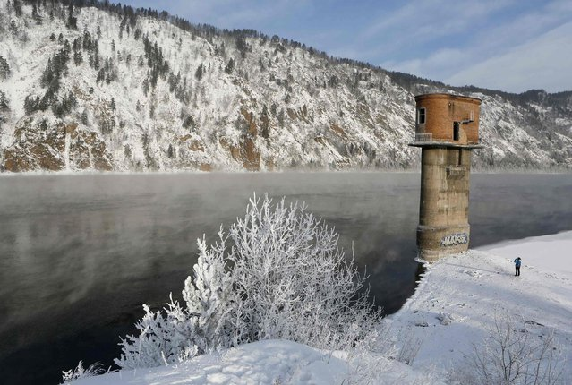 A woman takes a picture of an abandoned pump tower on the bank of the Yenisei River, with the air temperature at about minus 30 degrees Celsius, outside the Russian Siberian city of Krasnoyarsk, January 27, 2015. (Photo by Ilya Naymushin/Reuters)