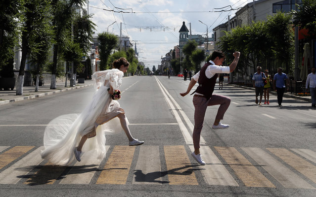 Newlyweds pose on a zebra crossing for wedding photographers during the 2018 soccer World Cup in Samara, Russia, Sunday, July 8, 2018. (Photo by Frank Augstein/AP Photo)