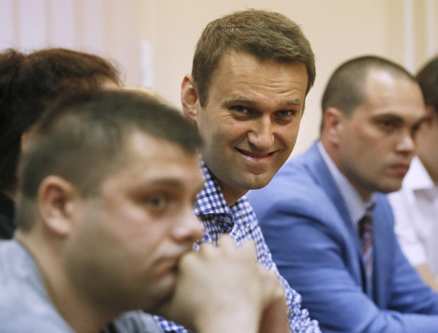 Russian opposition leader Alexei Navalny,  center, and his former colleague Pyotr Ofitserov, foreground, listen to judge in a court in Kirov, Russia on Thursday, July 18, 2013. A Russian judge on Thursday found Navalny guilty of embezzlement, a finding that could bring the charismatic anti-corruption blogger and Moscow mayoral candidate up to six years in prison. (Photo by Dmitry Lovetsky/AP Photo)